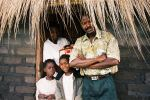 Edwin, his wife, baby, daughter (and her friend) outside their one room home