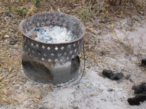Fill the mbaula with charcoal bought from roadside, light (just like that of course) and swing to and fro by the handle to get it going, then put on ground and cook