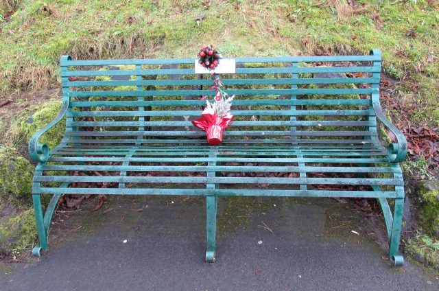 A bench in one of our local parks, just after Christmas, with floral tributes to memory of the person commemorated ion the plaque